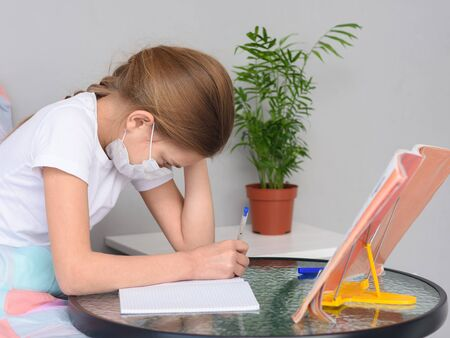 A girl in a medical mask does homework at a table in front of the bed Foto de archivo