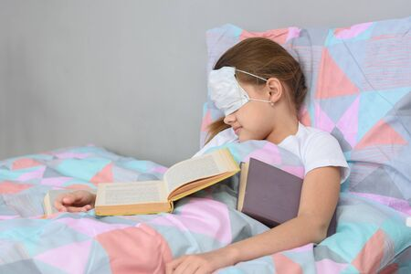 The sick girl fell asleep lying in bed and pulled the mask over her face Banco de Imagens