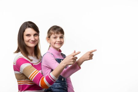 A girl sits on her mothers lap and joyfully points a finger at an empty place, looks into the frame