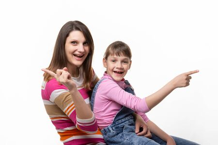Joyful mom and daughter point finger in different directions, isolated on white background