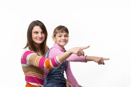 Mom and girl point a finger to an empty place