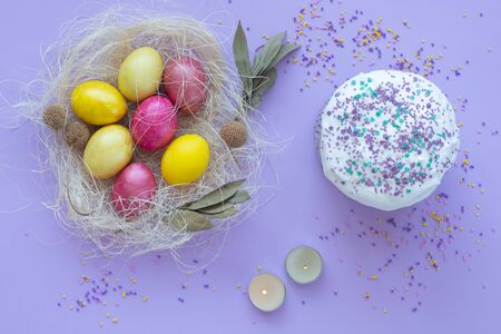 Easter eggs in the nest, cake, candles on a purple background