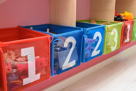 multi-colored boxes with numbers filled with little things Foto de archivo