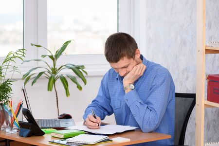 Pensive employee reads business papers in the office