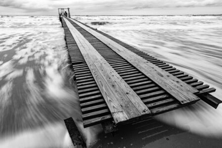 Long distance pier on the sea coast, black and white photo, long exposure Stock Photo