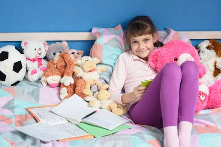 Girl among toys sits on the bed and does her homework