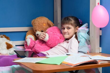 Girl's lip lying on the bed with soft toys and textbooks in the foreground Foto de archivo