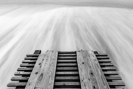 A breaking pier and surf washed out with a long exposure, black and white photo Foto de archivo