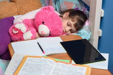 Girl sleeps with a teddy bear near a desk with textbooks and a tablet
