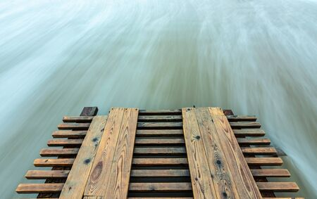 Broken pier and surf washed out with long exposure Foto de archivo