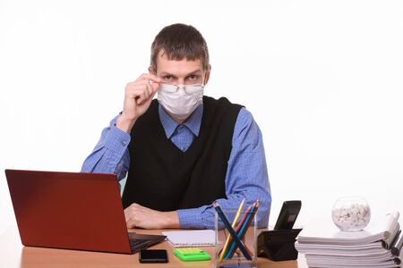 Clerk in a medical mask lowered his glasses from eye to nose