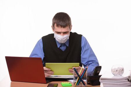 Office worker in a medical mask at the workplace looks at the tablet screen