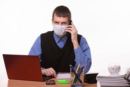 The clerk in a medical mask is talking on the phone and looked in the frame