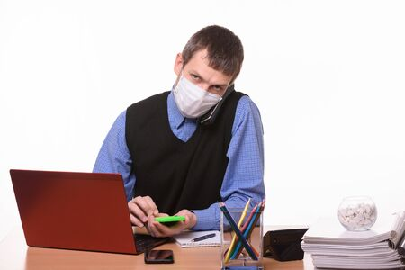 An office worker in a protective medical mask is talking on the phone, counting on a calculator and looking at the frame