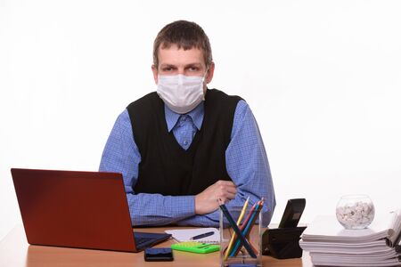 Office specialist in a protective medical mask sits at a desk and looks into the frame