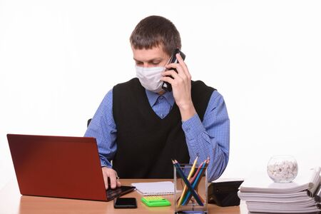 Clerk in a medical mask talking on the phone and working in a computer