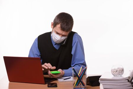 An office employee in a protective medical mask is talking on the phone, counting on a calculator