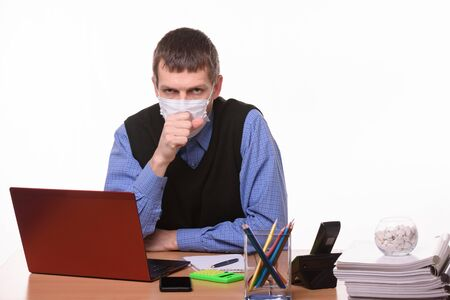 Office worker in a protective mask coughs in the office Foto de archivo