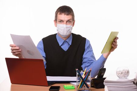 A man in a medical mask holds a paper document in one hand, and a tablet computer in the other Foto de archivo