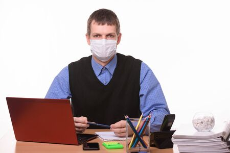 Portrait of a male office worker in a protective medical mask at the workplace