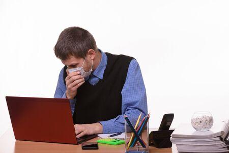 Office worker in medical mask sneezes at workplace Foto de archivo