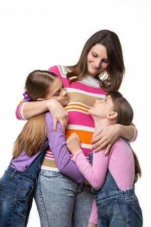 Children joyfully hug mom, isolated on white background Standard-Bild