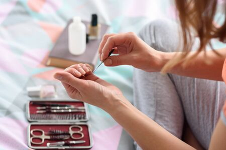 A girl files nails with a nail file, cosmetics in the background