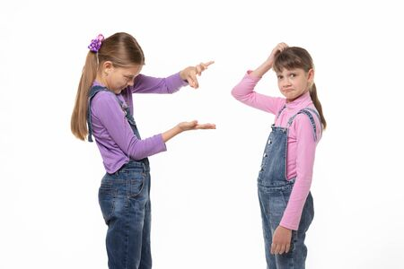 A girl shows a virtual object on her hand, another girl scratches her head in bewilderment