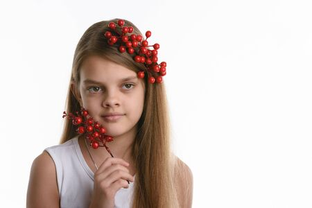 Portrait of a girl with a bunch of berries in her hair, as well as with a bunch in her hand