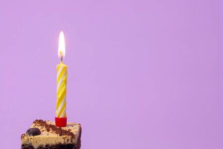 Festive burning candle on a cake on a light purple background Standard-Bild