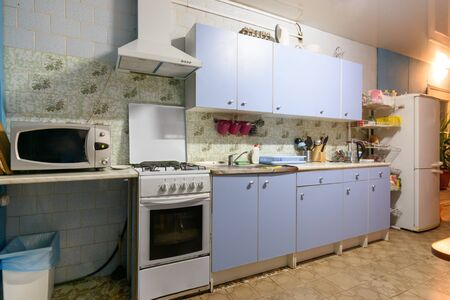 outdated kitchen interior with a hundred finishes and a simple kitchen set Foto de archivo