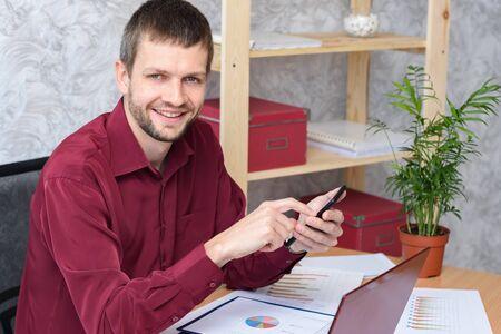 Smiling office worker corresponds on his smartphone 写真素材