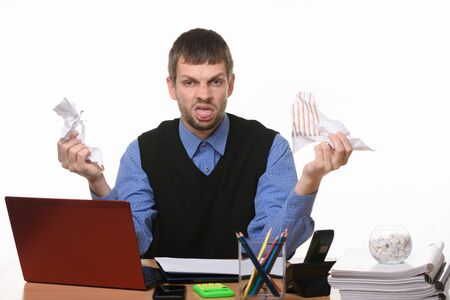 Man at work desk holds crumpled sheets of paper and shows tongue