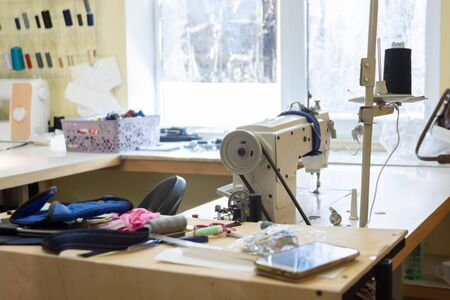 seamstresses in workshop with industrial sewing equipment