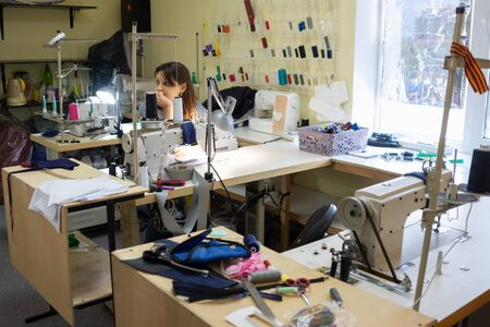 girl with a bored and dejected look at the workplace in a sewing workshop
