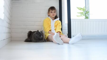 An upset girl in a yellow bathrobe sits in the corner of the room, a dark gray domestic cat sits nearby