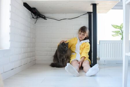 Punished girl sitting under the table and stroking a domestic cat