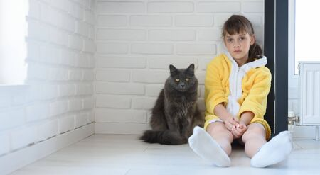 The punished girl sits in the corner of the room, a large domestic cat sits nearby