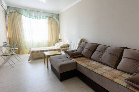 The interior of the bedroom in the apartment with a large sofa