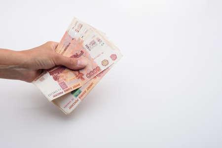 Hand holds a bundle of Russian five thousandth bills