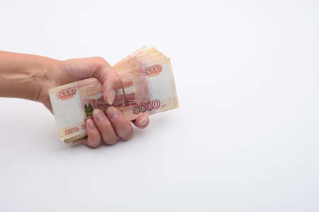Hand holds a stack of five thousandth bills in a fist