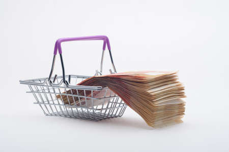 There is a large stack of bills on a grocery basket, viewed from the side