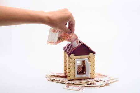 Hand shoves a five thousandth bill into the roof of a house Reklamní fotografie