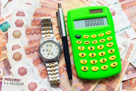 Against the background of Russian five-thousandth bills lies a calculator with the number one million, a watch and a pen Фото со стока