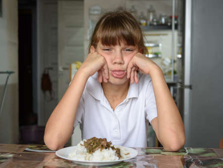 The girl refuses the food offered and shows her tongue