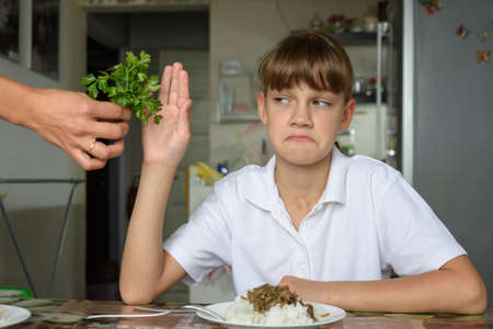The girl does not want to eat fresh herbs at lunch Imagens