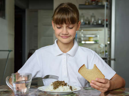 The girl is having dinner at the table, she looked at the food with appetite