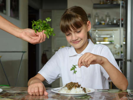 Girl sprinkles fresh herbs on the second dish for lunch