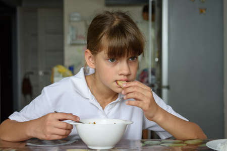 Tired hungry schoolgirl eating soup at the table in the kitchen