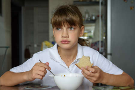 Girl thoughtfully eats soup at the table in the kitchen Standard-Bild